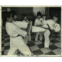 1978 Press Photo Karate student kicks wood slab while others look on - nob81931
