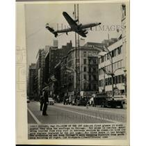1960 Press Photo A plane is lowered atop a roof on a building in Chicago