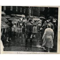 1961 Press Photo Pedestrians Raincoats Umbrellas - RRW04469
