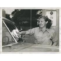 Press Photo woman cleaning the windshield of her car at gas station - RSH96091