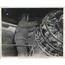 1948 Press Photo A man works on plane engine at Elgin Field in cold weather
