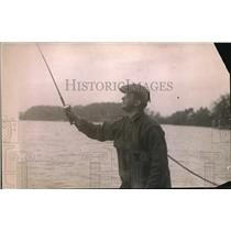 1919 Press Photo A man out fishing from a lake side