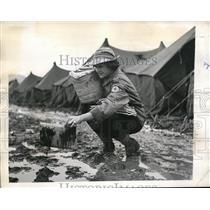 1943 Press Photo Nancy Gres Picks Up Mud Covered Magazine - ned17193