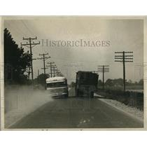 1929 Press Photo A bus passing a trailer truck on a road