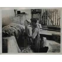 1936 Press Photo of a colonist drying wool in a native kettle - nee42605