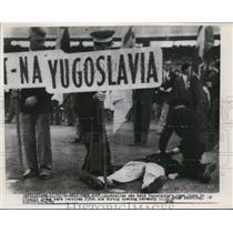 1956 Press Photo Yugoslavia Name Plate Holder Collapsed During Olympic Ceremony