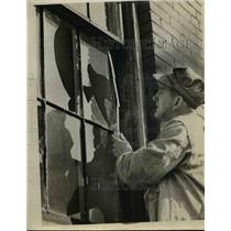 1943 Press Photo Custodian RA Panter fixes broken window at Trinity Lutheran