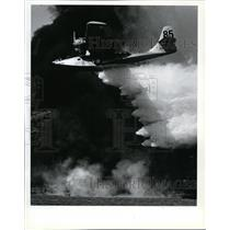 1993 Press Photo A tanker plane drops water on a fire near the runway