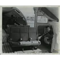 1966 Press Photo Two workers unlock planes's seat which are on carpeted pallets