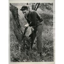 1940 Press Photo Boxer Ken Overlin saws wood at Madame Bey's camp while training