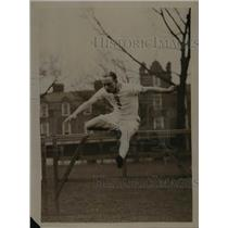 1921 Press Photo Track competitor J.F. Partridge jumps over a hurdle - net23446