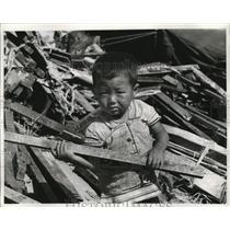 1961 Press Photo Boy in Korea carry wooden boards removed from their old shacks