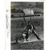 1985 Press Photo Scott Davenport landed with parachute and helped by Steve