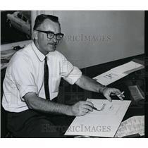1960 Press Photo Commercial Artist Luis Turner on paperwork - orb97260