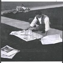 1959 Press Photo Newspaper Boy Picking Up Dropped Paper