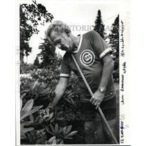 1988 Press Photo John Zarnekee tending his garden plants wearing his uniform