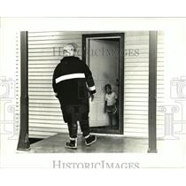 1986 Press Photo Marcellus Bron with fireman telling family they must evacuate
