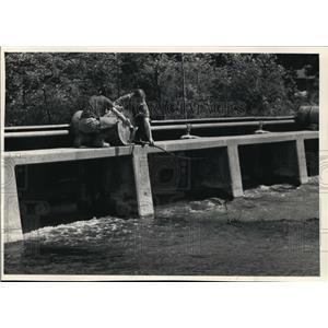1987 Press Photo Workers trickle detoxificant into the Oconomowoc River.