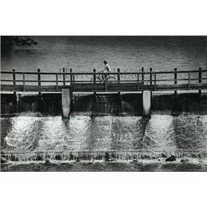 1983 Press Photo Ken Firari, of Lowell, rode a bike over Beaver Dam River.