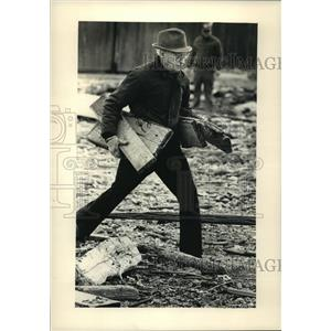 1987 Press Photo Man collects wood after a winter storm on shores of Lake Mich.