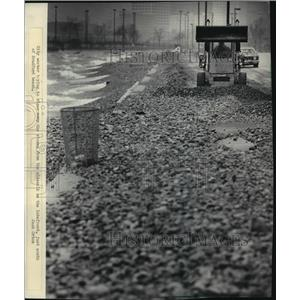 1987 Press Photo Clean Up, worker clearing away rocks at McKinley Beach.