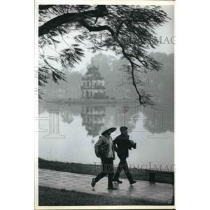 1990 Press Photo Temple Reflected in Lake in Hanoi, Vietnam as Couple Walks By.