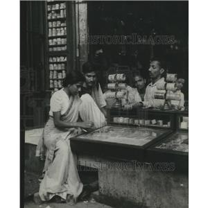 1949 Press Photo India, Susharan helps wife select some trinkets for souvenirs