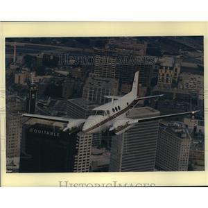 Press Photo A Beech King Air C90B aircraft flies over the city of Atlanta