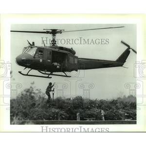 Press Photo A Louisiana guardsman attaches Christmas trees to a helicopter