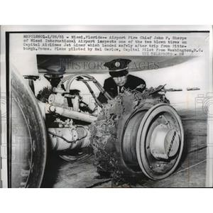 1961 Press Photo Airport Fire Chief J.F. Sharpe inspects tire Capital Airlines