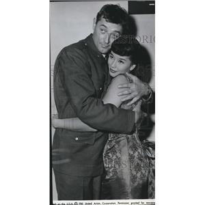 1961 Press Photo France Nuyen being cuddled by Bob Mitchum