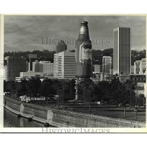 1984 Press Photo Bottle Shaped hot air balloon seems larger than buildings.