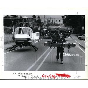 1990 Press Photo Ted Farr Carries a Stretcher from the Helicopter - orb73445