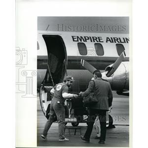 1989 Press Photo Empire Airlines employee Ken Watson helps passengers on flight.