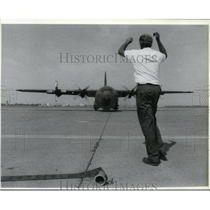 1988 Press Photo Brian Helwig directs a C-130 toward a hangar at Geiger Field