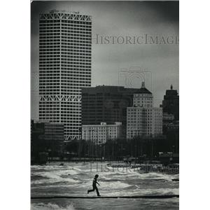1985 Press Photo Visitor runs along a jetty on Milwaukee's churning lakefront